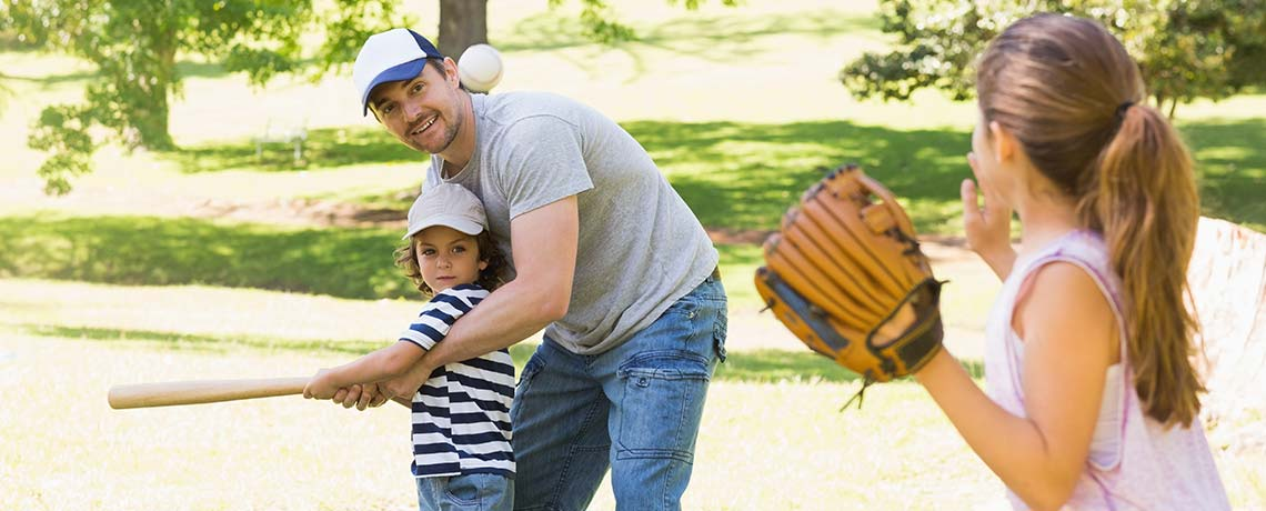 A father, son, and daughter playing baseball together