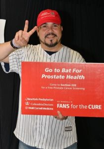 Yankees fan holding a Fans for the Cure poster